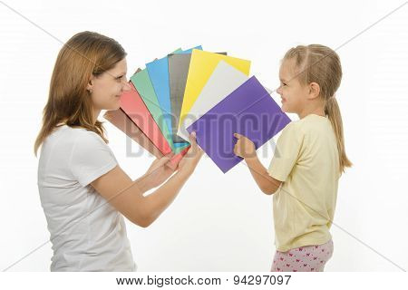 Child Shows Colors The Image In Hands Of Women