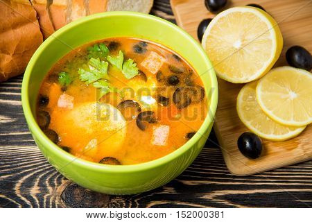 Traditional Russian soup solyanka in green bowl on wooden table