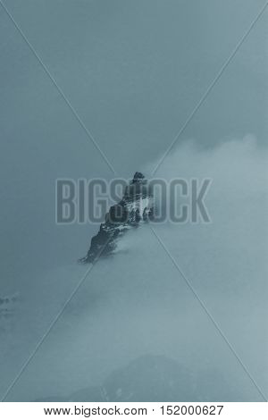 Pilot Peak is visible as winds blow aside mist and clouds. Viewpoint is from Beartooth Highway in the Shoshone National Forest outside Yellowstone National Park in Wyoming USA;