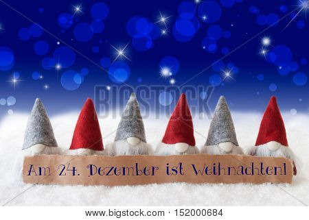 Label With German Text Am 24. Dezember Ist Weihnachten Means December 24th Is Christmas Eve. Christmas Greeting Card With Gnomes. Sparkling Bokeh And Blue Background With Snow And Stars.