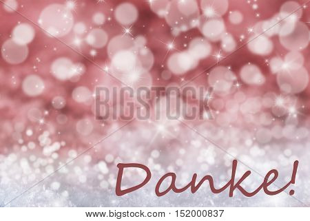 German Text Danke Means Thank You. Sparkling Red Bokeh Christmas Background Or Texture With Snow And Stars. Copy Space For Your Text Here