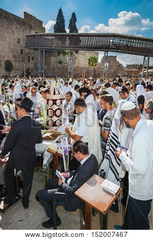 JERUSALEM, ISRAEL - OCTOBER 12, 2014:   Morning autumn Sukkot. The area in front of Western Wall of Temple filled with people. The Jews of ritual tallit worship with prayer books in their hands