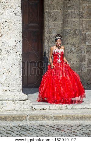 HAVANA CUBA - JULY 18 : Cuban woman with red dress in old Havana street on July 18 2016. The historic center of Havana is UNESCO World Heritage Site since 1982.
