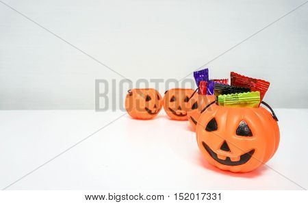 Orange pumpkin with colorful candies for Halloween party