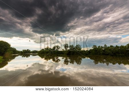Ominous stormy sky over natural lake, with dark red and grey cumulus clouds