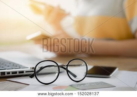 close up spectacles with young girl hand holding smart phone and laptop and credit card on wood desk in coffee shop. vintage effect. Release concept.