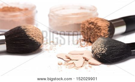 Crushed compact powder on the background of jars with loose cosmetic powder and makeup brushes. Side view, shallow depth of field