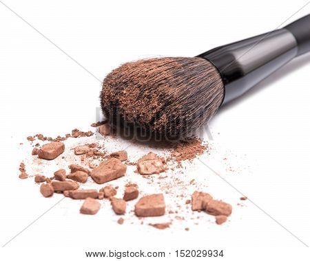 Close-up of makeup brush with crushed bronzing powder on white background. Bronzer to face contouring or creating tanned look. Shallow depth of field