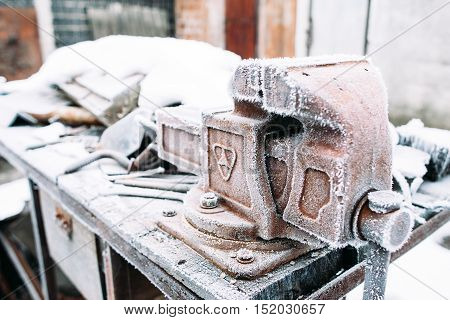 Vise stand on table covered with snow. Left outside tools in winter. Cold, early frosts, hoar, handyman concept