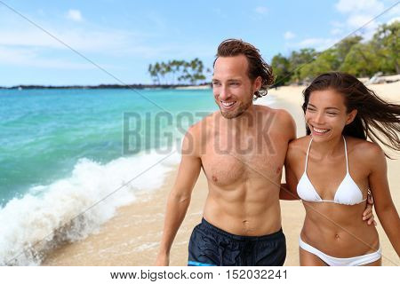 Beautiful sexy suntan people. Happy young interracial couple with slim and fit body relaxing walking on tropical paradise beach during summer vacation holiday. Travel relaxation sun skin care concept.