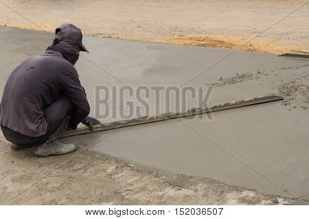Workman finishes and smooths concrete surface on new road. poster