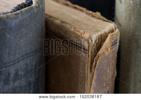 Different vintage antiquarian tattered books close up. Copy space