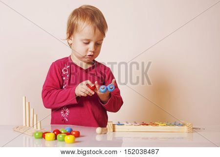 developmental toys for children ( little cute girl playing indoors )