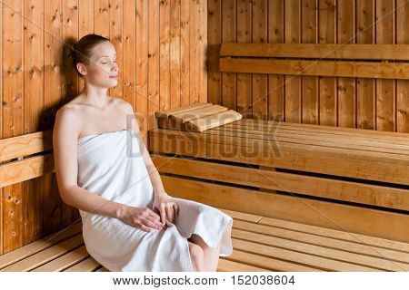 Young woman in wellness spa relaxing in wooden sauna