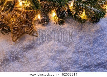 Christmas fir tree with lights and star on snow in dark, view from above