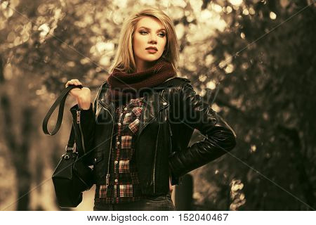 Young blond woman walking in autumn park. Fashion model in leather jacket outdoor