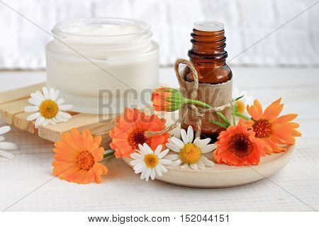 Fresh herbal skincare cosmetics. Essential oil, craft bottle, calendula flowers, jar facial cream. Natural beauty care remedy.