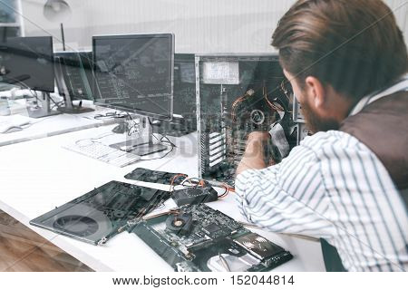 Electronic repairman working with CPU, double exposure. Unrecognizable engineer disassembling computer unit in repair shop