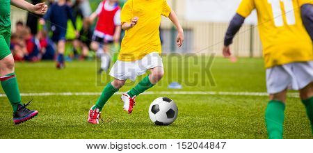 Young boys kicking soccer football on the sports field. Youth blue and green teams tournament competition. Youth soccer football background