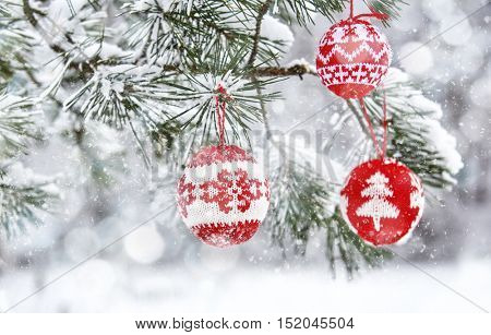 Merry Christmas and Happy Holiday! Christmas tree branch with baubles on a snowy winter background.