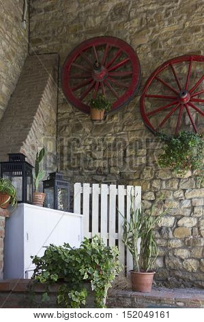 Vintage corner in an old style restaurant in Tuscany Italy with red wheels hung on the wall