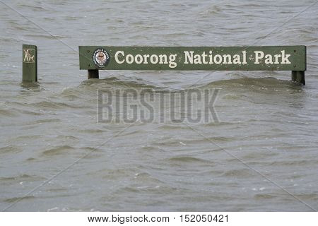 Hindmarsh Island South Australia Australia - October 11 2016: Coorong National Park sign submerged under the swollen Murray River due to flooding. Part of the Fleurieu Peninsula.