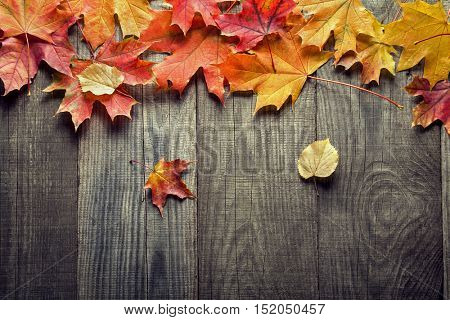 autumn leaf on wood black background (top view) orange leaf on old grunge wood deck, copy place for inscription, top view, tablet for text,