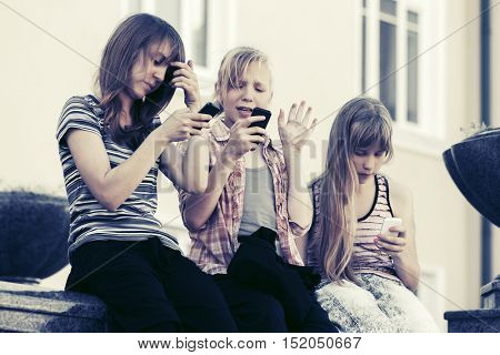 Group of happy teen girls calling on cell phones outdoor