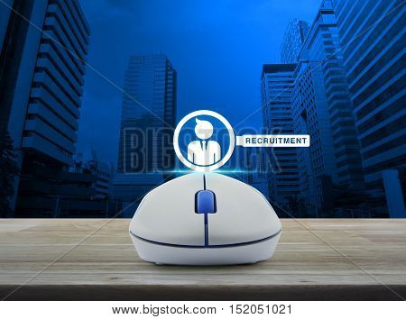 Wireless computer mouse with businessman and magnifying glass icon on wooden table over city tower Recruitment concept