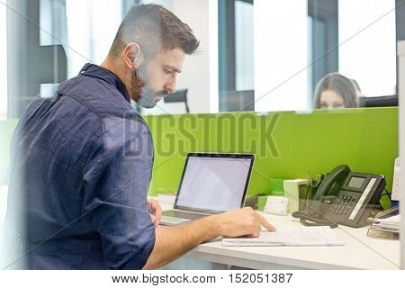 Mid adult businessman with laptop reading book at desk in office