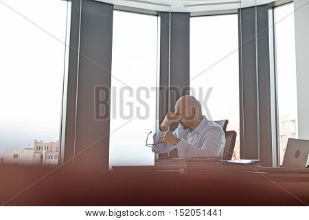 Tired mid adult businessman rubbing eyes in office