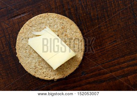 Single Scottish Oatcake With A Slice Of Yellow Cheese Isolated On Woden Desk From Above.