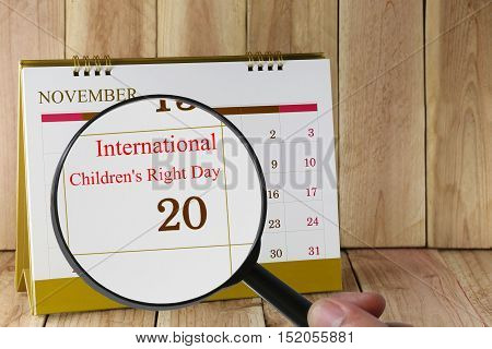 Magnifying glass in hand on calendar you can look International Children's Right Day 20 November concept of a public relations campaign.