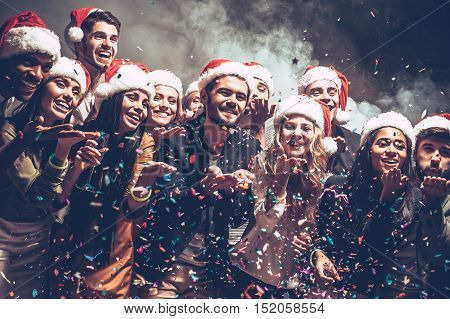 Little Christmas magic. Group of beautiful young people in Santa hats blowing colorful confetti and looking happy