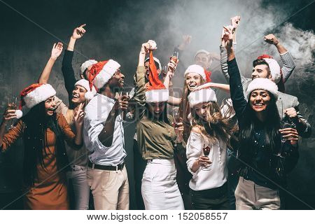 New Year party with friends. Group of beautiful young people in Santa hats dancing and looking happy