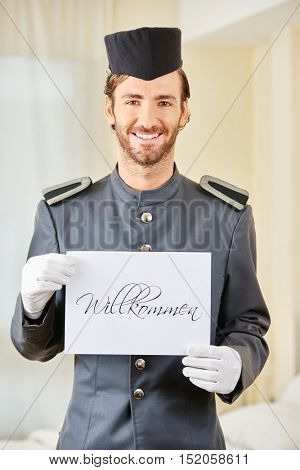 Smiling hotel page holding German sign saying