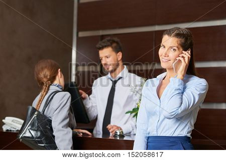 Friendly concierge serving hotel guests at reception