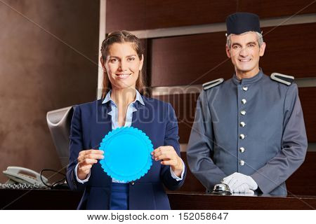 Helpful hotel staff with blue badge at hotel reception