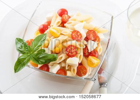 bright and tasty pasta salad with fresh mozarella and cherry tomatoes, basil