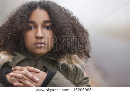 Beautiful mixed race African American girl teenager female young woman outside in autumn or fall mist or fog looking sad depressed or thoughtful