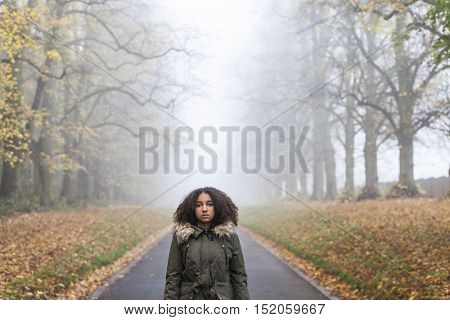 Beautiful mixed race African American girl teenager female young woman standing outside on a road in autumn or fall looking sad depressed or thoughtful