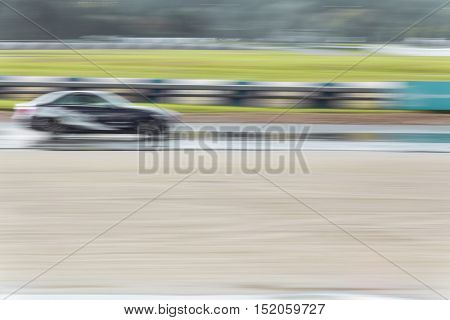 Motion blurred photograph of a car driving on a wet road at speed