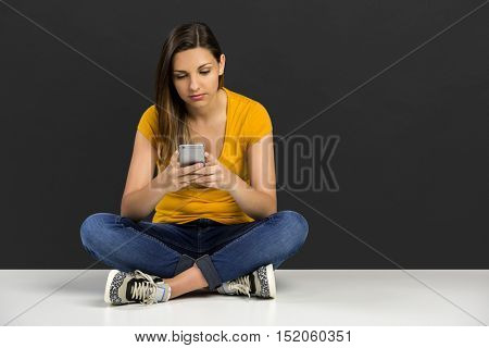 Beautiful woman sitting in the floor with her smarphone