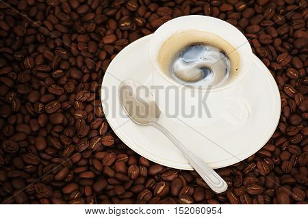 Cup of coffee with teaspoon on coffee beans background.