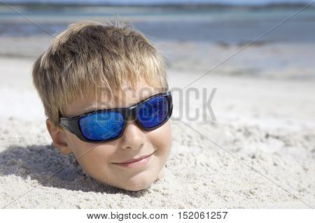 Boy on holiday buried in the sand