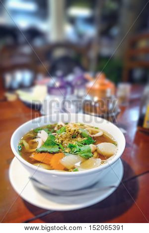 Hot and spicy Thai Dishes. Blurred image of a savoury thick soup made with squid rings spices and vegetables and crushed peanuts on cafe background. Vintage filter blur background with bokeh