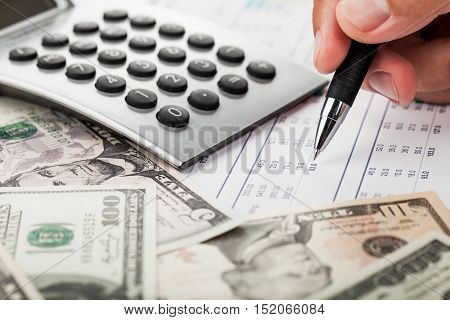 Close-up of a Businessman Analyzing Financial Figures with Calculator and Banknotes
