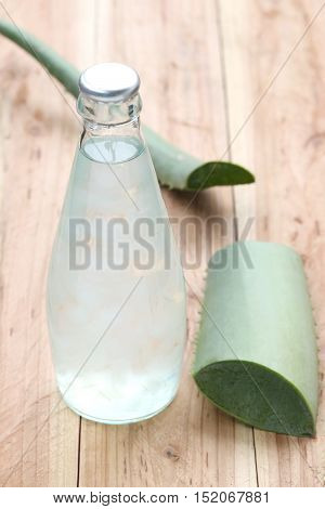 Aloe Vera jelly in the Glass bottles Near Aloe Vera plant on wooden tableconcept of healthy and organic food.