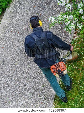 Houilles, France - April 08, 2014 : gardener using corded string trimmer in a park