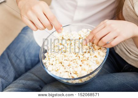Detail of a couple eating popcorn